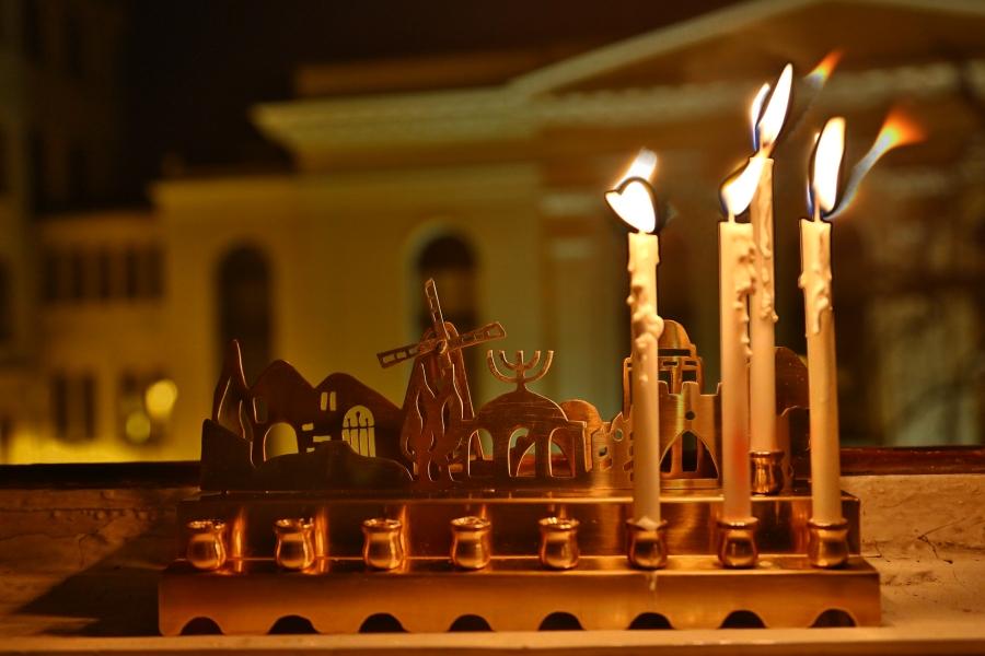 Trzecia chanukowa świeca w oknie naszej redakcji. W tle synagoga Pod Białym Bocianem.