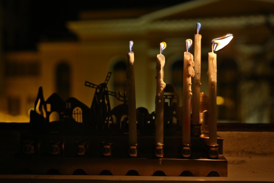 Czwarta chanukowa świeca w oknie naszej redakcji. W tle synagoga Pod Białym Bocianem.