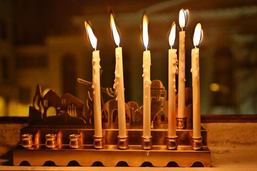 Pięć chanukowych świec w oknie naszej redakcji. W tle synagoga Pod Białym Bocianem.