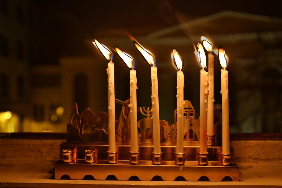 Sześć chanukowych świec w oknie naszej redakcji. W tle synagoga Pod Białym Bocianem.