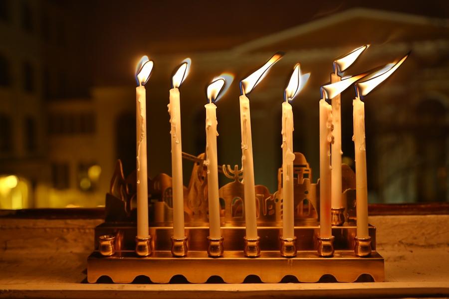 Siódma, przedostatnia świeca zapłonęła w oknie naszej redakcji. W tle synagoga Pod Białym Bocianem.
